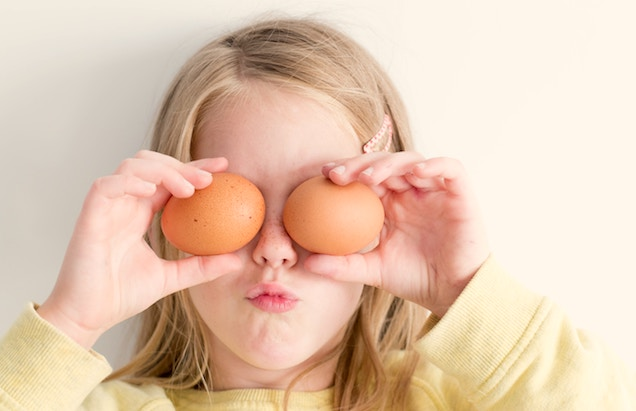 young girl holding eggs to eyes home