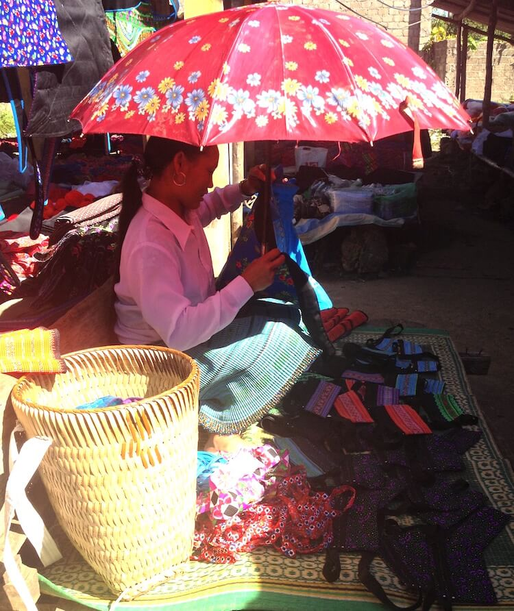 woman selling goods under an umbrella