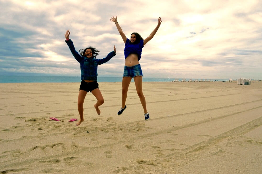 two sisters jumping happy beach