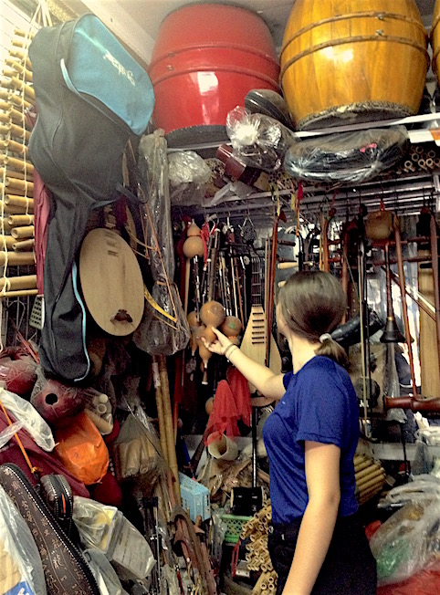girl looking at musical instruments shop hanoi