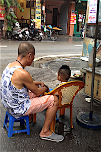 man and boy sitting on street hanoi