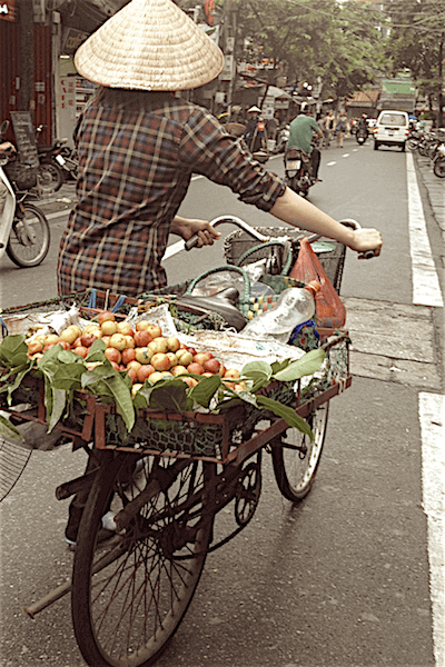 man on bicycle with flowers in the back hanoi