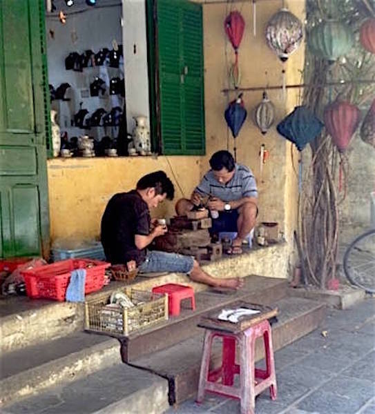 two men sitting in front shop hoian