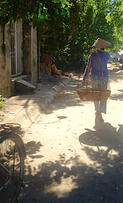 woman carrying baskets on shoulder