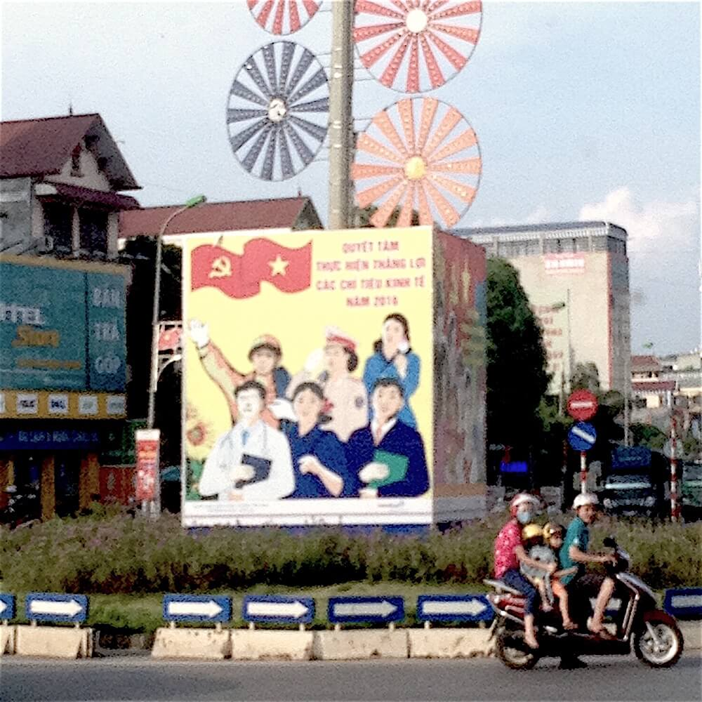 mai chau intersection billboard and family on motorbike