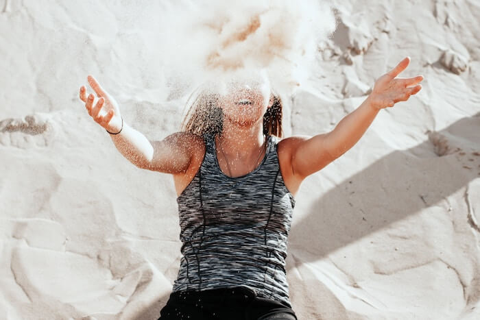 simple living woman throwing sand honest
