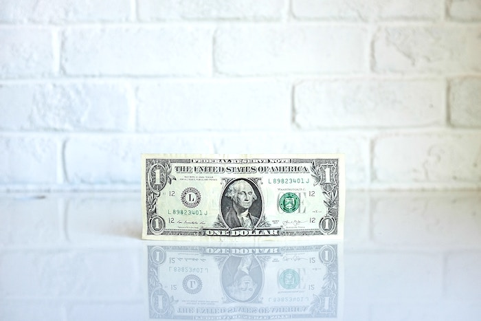 dollar bill against white wall simple living lifestyle