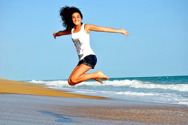 woman jumping with joy on beach simple living
