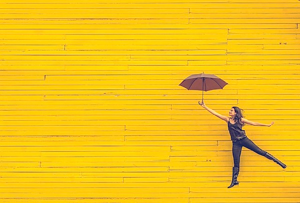 yellow wall with woman with umbrella simple living lifestyle