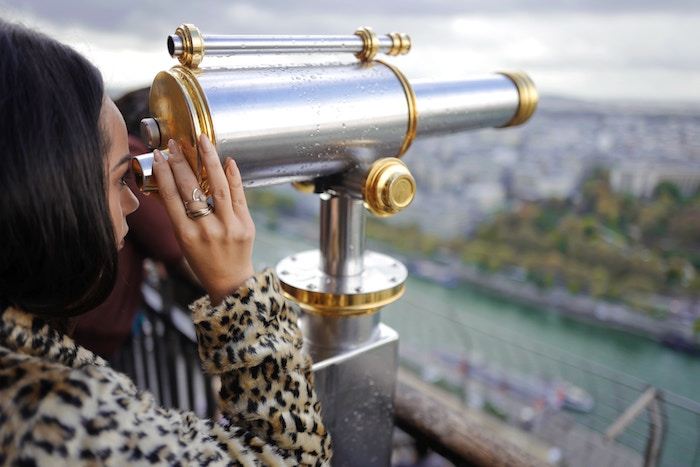 woman looking through telescope simple living