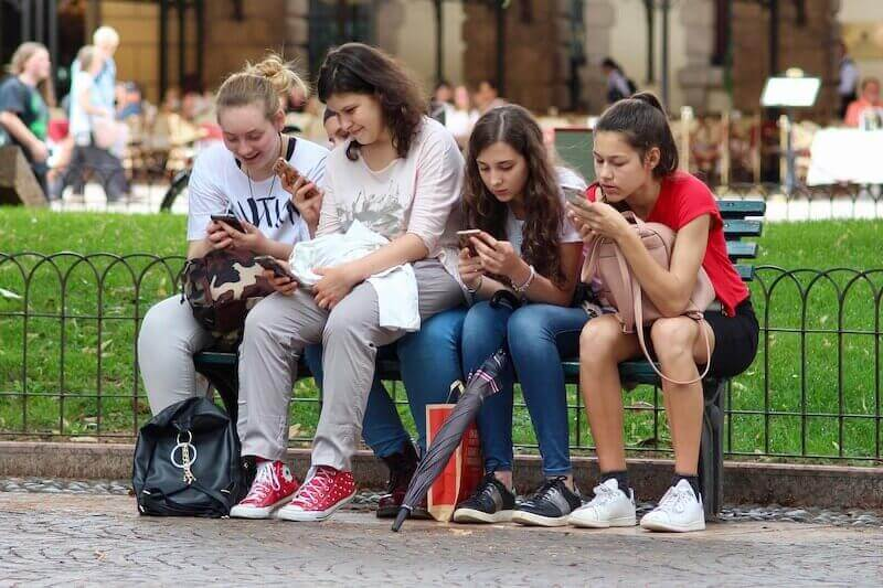 teens in park with phone