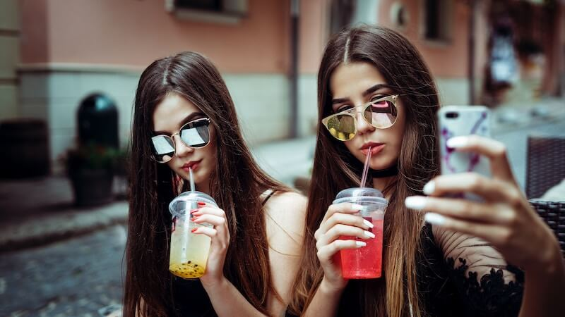 two girls with phones and sunglasses