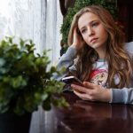 girl sitting at table with phone